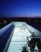 Roof terrace lit by transparent floor under an evening sky in the city