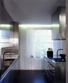 Cord curtain in front of lattice window in minimalist stainless steel kitchen with two worktops