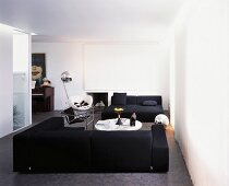 White modern living room with black seating on a grey floor