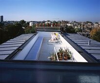 Reading person on lounger on long roof terrace with incredible panoramic views over city