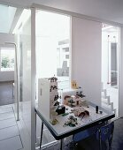 Desk with architecture models in front of ceiling-height windows with view of stairwell