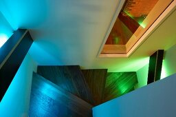 Wood-clad handrails shedding indirect coloured light on a winding wooden stairway with view through an interior window