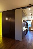 Central stairwell, bath and kitchen unit in London loft apartment with wall-to-wall wooden flooring