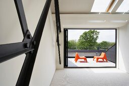 View from empty interior room with metal girders through open window wall to roof terrace with two orange plastic chairs