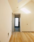 View of doors in white walk-in closet with light wooden floorboards and sun falling through skylight