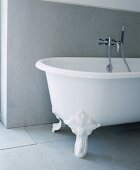 Free-standing bathtub with claw feet and modern taps on matte, grey tiles in front of grey wall cladding