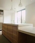 Kitchen unit in warm tones with simple wood front and stone worktops at different heights under pendant lights