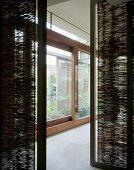 View between bamboo matting partitions onto extensive glass sliding doors