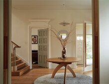 Round wooden table with a frame of quarter-circle legs on a round rug in the light foyer of an English house