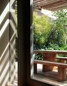 Sunbeams through wooden pergola above garden terrace with simple seating made from heavy wooden boards