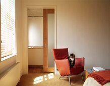 Cat on designer leather chair in bedroom in natural shades with sliding door leading to ensuite bathroom