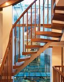 Open apartment stairs with wooden treads and metal supports in front of reflective window