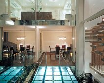 Bridge of illuminated glass bricks with view of rooms between reflective glass panels in English house