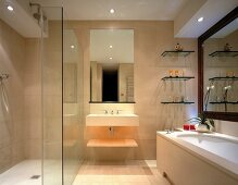 Bathroom completely tiled in stone with floor-level shower and large mirror