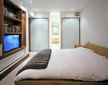 Wall cabinet with TV on opposite double bed in modern bedroom with ensuite bathroom