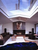 Leather seating in front of chimney breast with large portrait and deep blue furniture with tangled cushions under a skylight showing a view of a blue city sky