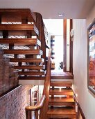 Two flights of wooden stairs next to brick wall with view of open-plan, traditional living room