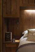 Bed in front of wood-clad wall with indirect lighting and wooden wall cupboards