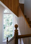 Traditional stairwell with arched window and modern wooden stairs with solid balustrade