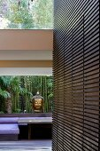Wood-clad wall with integrated fitted cupboard and head of Buddha on windowsill