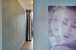 Portrait of a woman on a wall next to an open hallway with fitted cupboards