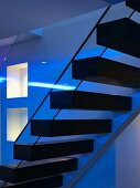 Contemporary stairs with floating wooden treads in low lighting