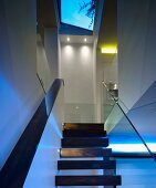 Wooden stairs in open stairwell with skylight in contemporary house