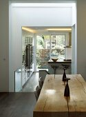 Rustic wooden table with wide doorway and view of modern kitchen