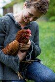 Frau hält lebendiges Huhn