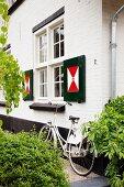 Hollandrad vor weisser Backsteinfassade mit auffällig bemalten Fensterläden