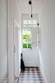 Klassische, diagonal verlegte Schachbrettfliesen im renovierten Altbauflur eines kleinen Landhauses
