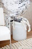 Rücklings auf einer Metalltonne liegende schwarzweisse Stoffpuppen vor Stoffgemälde und Armlehnstuhl auf Strickteppich