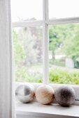 Dekokugeln aus Stein auf weißem Fensterbrett