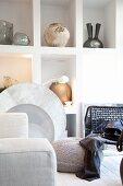 weiße Wandnischen mit verschiedenen Vasen und Sitzmöbel in Grautönen im Vordergrund