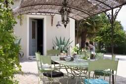 Hellgrün lackierte Metallstühle und Tisch im Retrostil unter Pergola mit Strohdach vor Wohnhaus und im Hintergrund Frau bei Gartenarbeit
