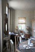 Stühle mit geschwungener Lehne an rustikalem Esstisch mit Vintage Frühstücksgeschirr in offenem Wohnzimmer mit Salonecke und Rokokostühlchen