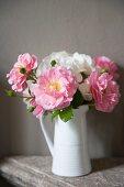 Blumenstrauss mit weissen und rosa Rosen in Vintage Porzellankrug vor grauer Wand