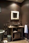 Badezimmerecke mit rustikalem Waschtisch und aufgesetzter Keramikschüssel neben Designerarmatur unter Wandspiegel an dunkelgrau getönter Wand