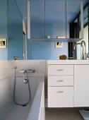 Modern bathroom with bathtub next to white washstand below large mirror on wall