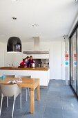 Offene Küche mit hängender Dunstabzugshaube und Edelstahlgeräten