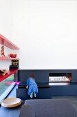 Wohnzimmer mit modernem Kamin und roten Wandregalen über Fensterband