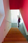 Treppenabgang und Blick auf Rote Wand und Flur mit Natursteinboden
