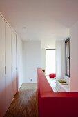 Rote halbhohe Wand im Flur mit Parkettboden