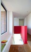 Blick auf Treppenabgang mit halbhoher roter Wand