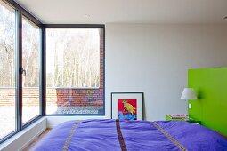 Schlafzimmer mit Panoramafenster und Blick auf sonniger Terrasse
