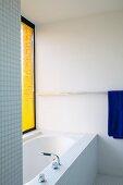 Badewanne im Bad mit Mosaikfliesen und gelbe Jalousien
