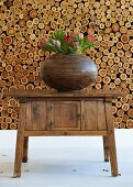 Brown striped, pot belly vase holding exotic protea flowers on old wooden wall table with neatly-stacked firewood in background