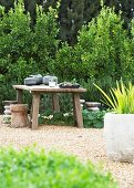 Rustic table with four stools on area of gravel in garden
