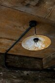 Vintage pendant lamp with rusty lampshade hanging from wooden ceiling