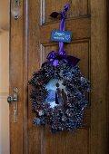 Festive wreath of pine cones on wooden door